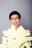 Le asiatisk man klistrade klistermärkear Arkivbild