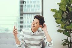 Le asiatiskt stiligt mansammanträde på den mysiga soffan som lyssnar till musen arkivfoto