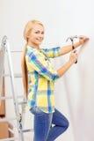 Le att bulta för kvinna spika i vägg fotografering för bildbyråer