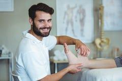 Le att sätta för fysioterapeut förbinda på sårad fot av patienten Arkivfoton