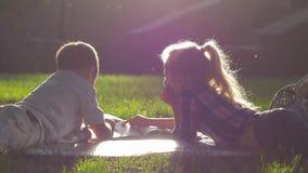 Le attività di tempo libero, bambini curiosi osservano le immagini in libro durante la pausa della scuola che si trova sull'erba  video d archivio