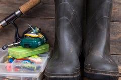 Le attrezzature di pesca e gli stivali di gomma su legname imbarcano Immagine Stock Libera da Diritti