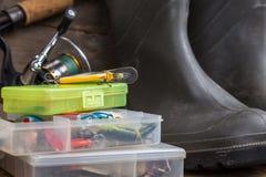 Le attrezzature di pesca e gli stivali di gomma su legname imbarcano Fotografie Stock