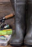Le attrezzature di pesca e gli stivali di gomma su legname imbarcano Fotografia Stock Libera da Diritti