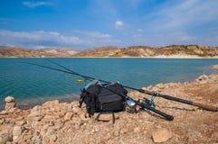 Le attrezzature di pesca si trovano su una riva del lago immagini stock libere da diritti