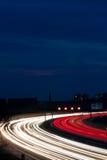 Le automobili avévano luogo nella notte su una strada principale Fotografia Stock