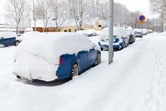 Le automobili coperte di neve hanno parcheggiato lungo la via nevosa Fotografia Stock Libera da Diritti