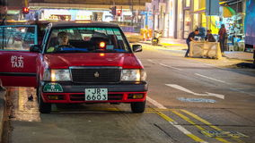 Le automobili del taxi serviscono i passeggeri sul lasso di tempo della via della città di sera Hon Kong stock footage