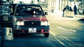 Le automobili del taxi serviscono i passeggeri sulla via della città di sera Lasso di tempo Hon Kong archivi video