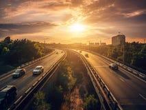 Le automobili di traffico urbano guidano al tramonto sulla strada principale nella scena dell'estate di paesaggio urbano, concett fotografia stock
