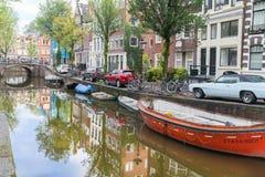 Le automobili e le biciclette parcheggiate lungo la via hanno riflesso con le costruzioni sopra le barche attraccate in canale Fotografie Stock Libere da Diritti