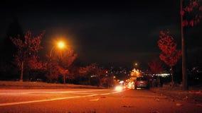 Le automobili guidano giù la collina in città alla notte video d archivio