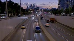 Le automobili guidano lungo la via per scavare una galleria contro le siluette della città archivi video