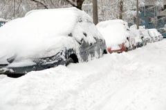 Le automobili innevate hanno allineato nella via della città nell'inverno Immagini Stock