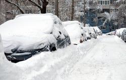 Le automobili innevate hanno allineato nella via della città nell'inverno Fotografia Stock Libera da Diritti