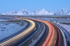 Le automobili rosse e gialle trascina sulla strada principale con le montagne sull'orizzonte Fotografie Stock Libere da Diritti