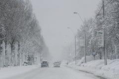 Le automobili sono vedute su una strada, durante precipitazioni nevose fotografia stock libera da diritti