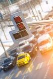 Le automobili stanno ad un'intersezione fino agli spettacoli di luci di traffico rossi Fotografia Stock