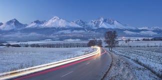 Le automobili trascina sulla strada alle montagne Fotografia Stock