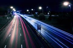 Luci delle automobili sulla via di Londra entro la notte Fotografia Stock Libera da Diritti
