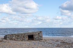 Le bâtiment de la défense de plage WW2 a découvert par la montée subite de marée photographie stock libre de droits