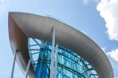 Le bâtiment en verre sous forme de bateau contre le ciel bleu avec des nuages Images stock