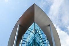 Le bâtiment en verre sous forme de bateau contre le ciel bleu avec des nuages Images libres de droits