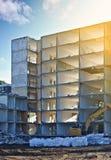 Le bâtiment résidentiel démoli avec des sachets d'excavatrice et en plastique a rempli de blocaille dans le premier plan Photo libre de droits