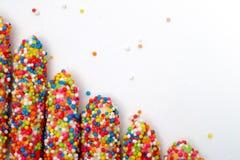 Le bâton coloré de biscuit a enduit le sucre d'arc-en-ciel d'émail du fond blanc de l'espace Photo libre de droits
