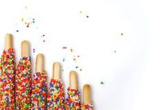 Le bâton coloré de biscuit a enduit le sucre d'arc-en-ciel d'émail du fond blanc de l'espace Image stock
