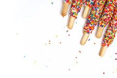 Le bâton coloré de biscuit a enduit le sucre d'arc-en-ciel d'émail du fond blanc de l'espace Photo stock