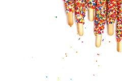 Le bâton coloré de biscuit a enduit le sucre d'arc-en-ciel d'émail du fond blanc de l'espace Photographie stock