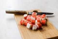 Le bâton découpé en tranches frais de crabe découpe Surimi en tranches sur le conseil en bois tout préparé photo libre de droits