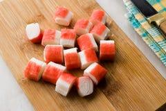 Le bâton découpé en tranches frais de crabe découpe Surimi en tranches sur le conseil en bois tout préparé photos stock