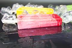 Le bâton de crème glacée avec le glaçon sur le fond noir photographie stock libre de droits