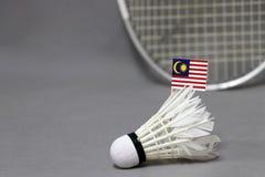 Le bâton de drapeau de Mini Malaysia sur le volant blanc sur le fond gris et focalisent la raquette de badminton image libre de droits