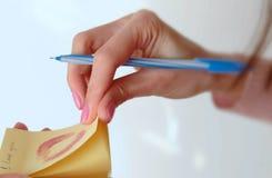 Le bâton de main du ` s de femme de plan rapproché la note avec le baiser et écrivent - je t'aime - sur le mur blanc Images stock