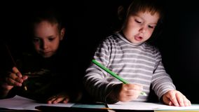 Le bébé émotif dessine un crayon avec son frère plus âgé, plan rapproché banque de vidéos