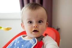 Le bébé étonné enduit de la nourriture, mange Photo libre de droits