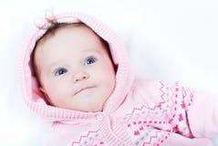 Le bébé adorable dans le rose a tricoté la veste avec les coeurs rouges Image stock