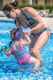 Le bébé apprennent à nager dans la piscine avec sa mère Image libre de droits