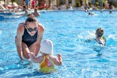Le bébé apprennent à nager dans la piscine avec sa mère Image stock