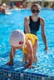 Le bébé apprennent à nager dans la piscine avec sa mère Images stock