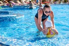Le bébé apprennent à nager dans la piscine avec sa mère Photos libres de droits