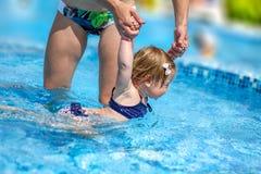 Le bébé apprennent à nager dans la piscine avec sa mère Photographie stock libre de droits