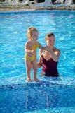 Le bébé apprennent à nager dans la piscine avec sa mère Photo stock