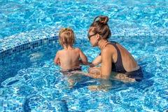 Le bébé apprennent à nager dans la piscine avec sa mère Photo libre de droits