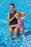 Le bébé apprennent à nager dans la piscine avec sa mère Photos stock