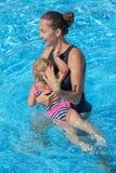 Le bébé apprennent à nager dans la piscine avec sa mère Photographie stock