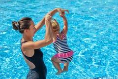 Le bébé apprennent à nager dans la piscine avec sa mère Images libres de droits